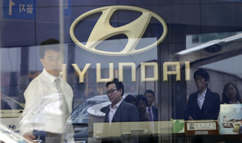 Pedestrians are reflected on the window of a Hyundai Motor's showroom in Seoul, South Korea, Thursday, Oct. 25, 2012. Hyundai Motor Co. suffered a fall in third quarter profit versus the previous quarter after strikes dented vehicle production. (AP Photo/Lee Jin-man)