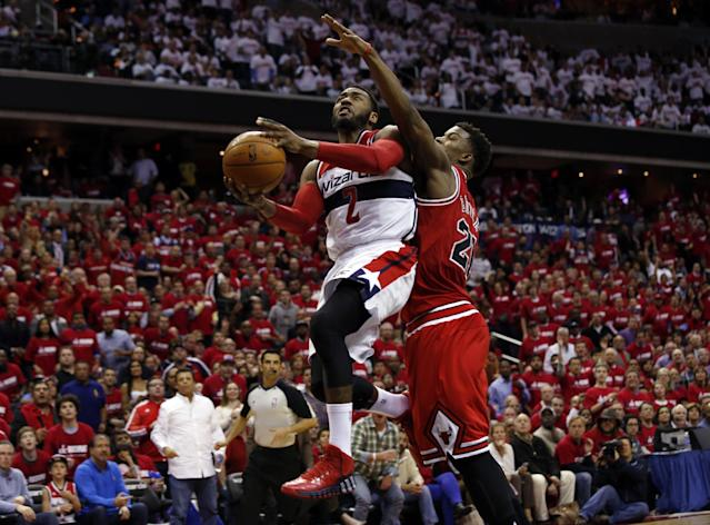 Washington Wizards guard John Wall (2) shoots past Chicago Bulls guard Jimmy Butler (21) in the second half of Game 3 of an opening-round NBA basketball playoff series on Friday, April 25, 2014, in Washington. The Bulls won 100-97. (AP Photo/Alex Brandon)
