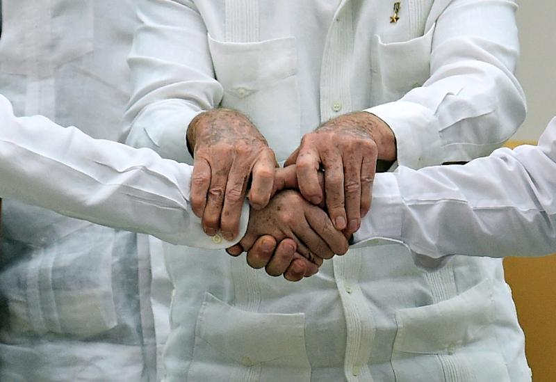 Colombian President Juan Manuel Santos (L) and the head of the FARC guerrilla group Timoleon Jimenez, aka Timochenko (R), shake hands as Cuban President Raul Castro (C) holds their hands during a meeting in Havana on September 23, 2015 (AFP Photo/Luis Acosta)