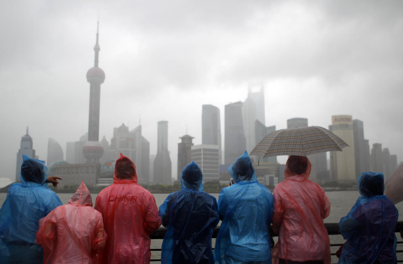 FILE - In this Aug. 7, 2011 file photo, tourists in colorful rain coats visit the Bund, one of the most popular tourist destinations in town, to view the city's famous skyscrapers across the Huangpu River in heavy rain and strong wind caused by Typhoon Muifa in Shanghai, China. Asian governments face a balancing act as they fight accelerating inflation while economic malaise in the U.S. and turmoil in financial markets threaten to dim the region's growth. Global stocks were battered this week by the first-ever downgrade of the U.S. credit rating and indicators pointed to stalling recoveries in the U.S. and Europe that could erode demand for Asia's exports of cars, gadgets, clothing and other goods. (AP Photo/Eugene Hoshiko, File)