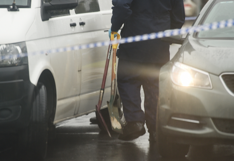 Detectives carry shovels to the home following the alleged assault of three children. Photo: AAP