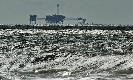 An oil and gas drilling platform stands offshore as waves churned from Tropical Storm Karen come ashore in Dauphin Island, Alabama