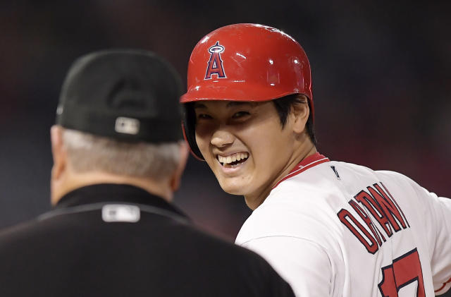 Los Angeles Angels' Shohei Ohtani, right, of Japan, smiles at first base umpire Joe West after hitting a single during the second inning of a baseball game against the Oakland Athletics, Friday, Sept. 28, 2018, in Anaheim, Calif. (AP Photo/Mark J. Terrill)