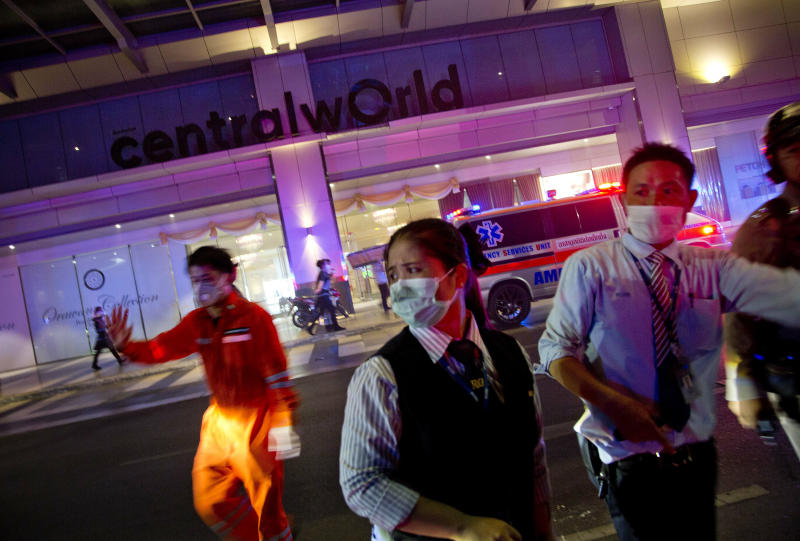 Rescue workers and mall staff try to control crowds at the scene of a fire outside the Central World mall complex in Bangkok, Thailand, Wednesday, April 10, 2019. A fire had broken out at the major mall complex in Thailand's capital, with initial reports from Thai emergency services saying it has caused numerous fatalities. (AP Photo/Gemunu Amarasinghe)