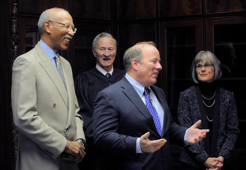 Former Detroit Mayor Dave Bing looks on as New Detroit Mayor Mike Duggan speaks with the media following the oath of office, New Years Day, Wednesday, Jan. 1, 2014, at the Coleman Young Municipal Center in Detroit. Judge Patrick James Duggan, Jr., the mayor's father and his wife Lori Maher are seen in the background. (AP Photo/The Detroit News, Steve Perez)