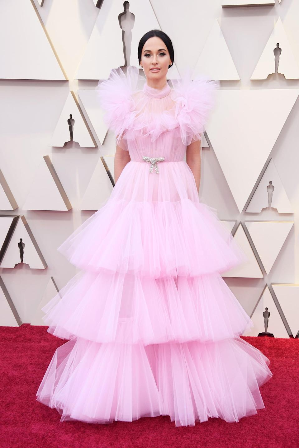 """<p><a rel=""""nofollow noopener"""" href=""""https://www.popsugar.com/fashion/Kacey-Musgraves-Dress-2019-Oscars-45832037"""" target=""""_blank"""" data-ylk=""""slk:Wearing a Giambattista Valli Haute Couture gown"""" class=""""link rapid-noclick-resp"""">Wearing a Giambattista Valli Haute Couture gown</a> with Brian Atwood shoes and a Jimmy Choo clutch.</p>"""