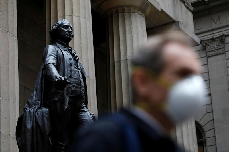 A man walks by a statue of first U.S. President George Washington on the steps of Federal Hall while wearing a surgical mask as more cases of coronavirus were confirmed in Manhattan, New York City, New York, U.S., March 12, 2020. REUTERS/Andrew Kelly