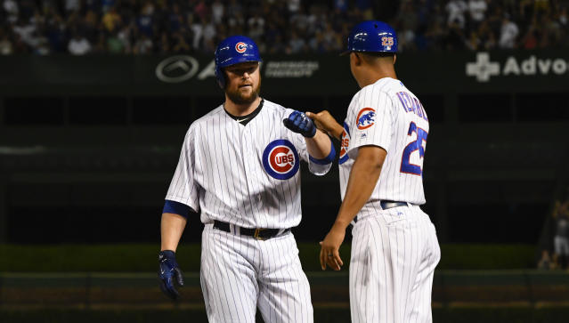 Chicago Cubs' Jon Lester, left, fist-bumps first base coach Will Venable (25) after his two-RBI single during the third inning of a baseball game against the New York Mets on Monday, Aug. 27, 2018, in Chicago. (AP Photo/Matt Marton)