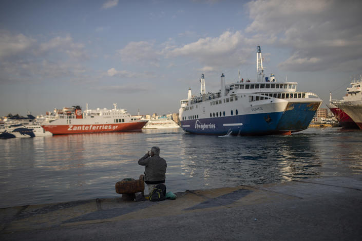 A man sits on the dock at the port of Piraeus, near Athens, on Monday, May 25, 2020. Greece restarted Monday regular ferry services to the islands as the country accelerated efforts to salvage its tourism season. (AP Photo/Petros Giannakouris)