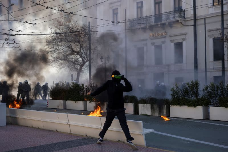 A protester throws a petrol bomb as Greek university students clash with riot police during a demonstration against government plans to set up university police, amid the coronavirus disease (COVID-19) pandemic, in Athens