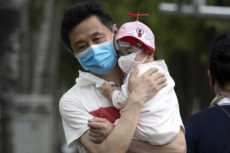 A man holds a child wearing masks to curb the spread of the coronavirus in Beijing on June 17. Source: AP