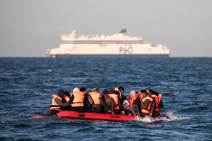 Migrants packed tightly onto a small inflatable boat bail water out as they attempt to cross the English Channel near the Dover Strait, the world's busiest shipping lane, on September 07, 2020 off the coast of Dover, England.
