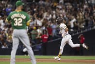 San Diego Padres' Fernando Tatis Jr., right, runs the bases after hitting a home run off Oakland Athletics starting pitcher James Kaprielian, left, during the third inning of a baseball game Tuesday, July 27, 2021, in San Diego. (AP Photo/Derrick Tuskan)