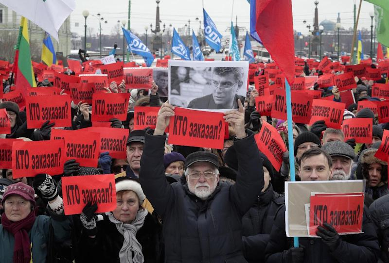 People hold posters reading 'Who ordered the murder?' during a rally in memory of opposition leader Boris Nemtsov in St. Petersburg, Russia, Sunday, Feb. 26, 2017. Thousands of Russians have taken to the streets of Moscow and St. Petersburg to mark two years since Nemtsov was gunned down outside the Kremlin. (AP Photo/Dmitri Lovetsky)