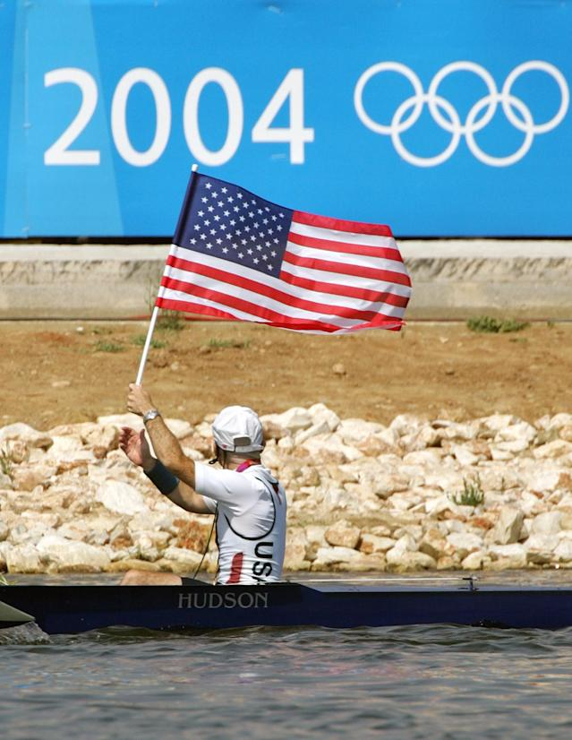 American Men's Eight coxswain Pete Cipollone carries the U.S. flag past an Olympic sign after they won the gold medal at the 2004 Olympic Games in Schinias near Athens, Greece, Sunday, Aug. 22, 2004. (AP Photo/Armando Franca)