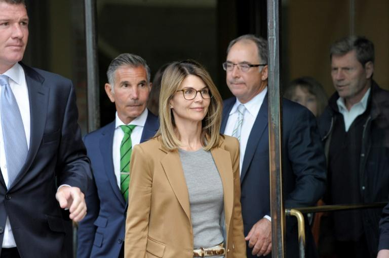 """Full House"" star Lori Loughlin (C) and her husband, designer Mossimo Giannulli (L), were among 50 people indicted in the wide-ranging college bribery scandal"