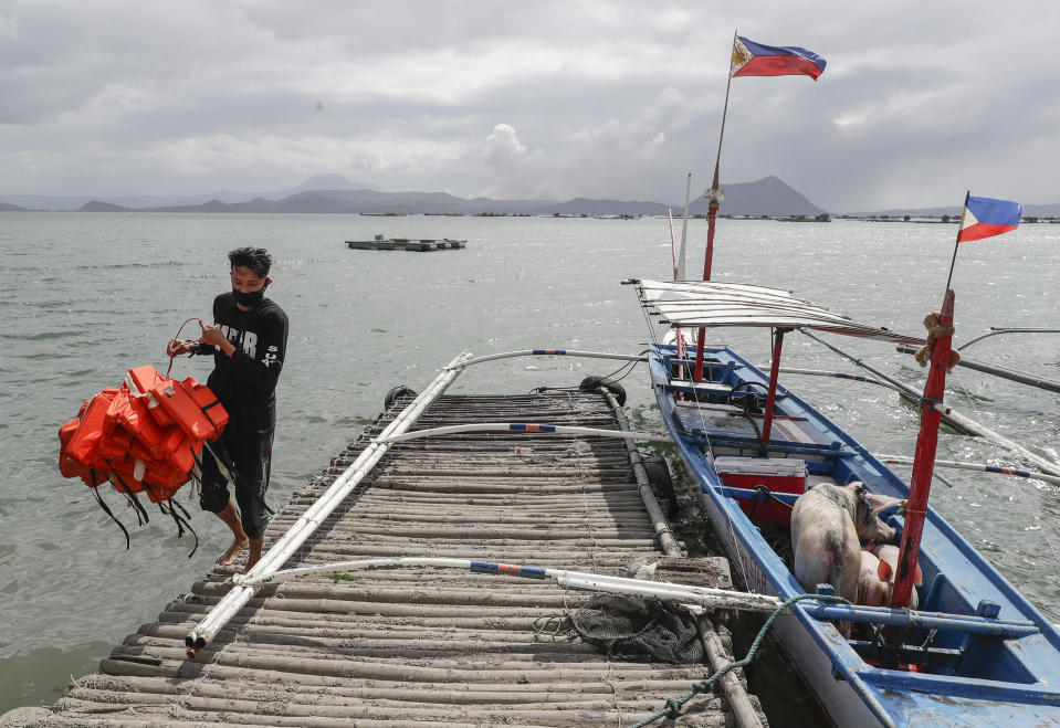In this Jan. 14, 2020, photo, Christian Morales carries life vests beside his pigs which they rescued across the lake in Talisay, Batangas province, southern Philippines, as Taal volcano continues to spew ash. So far no one has been reported killed in the eruption, but the disaster is spotlighting the longstanding dilemma of how the government can move settlements away from danger zones threatened by volcanoes, landslides, floods and typhoons in one of the world's most disaster-prone countries. (AP Photo/Aaron Favila)