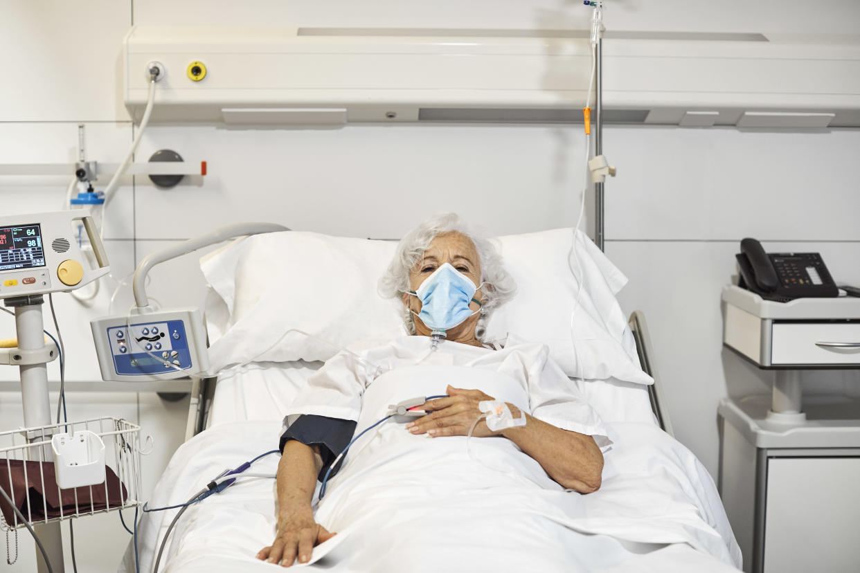 Portrait of senior woman with oxygen mask lying on bed. Elderly female patient is in intensive care unit during COVID-19. She is in hospital ward.