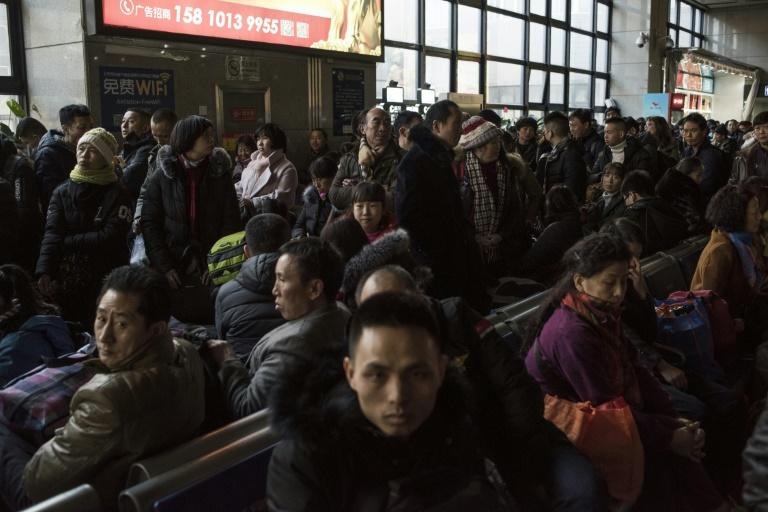 Travellers wait for a train at the West Railway Station in Beijing, as they depart the capital ahead of the Lunar New Year