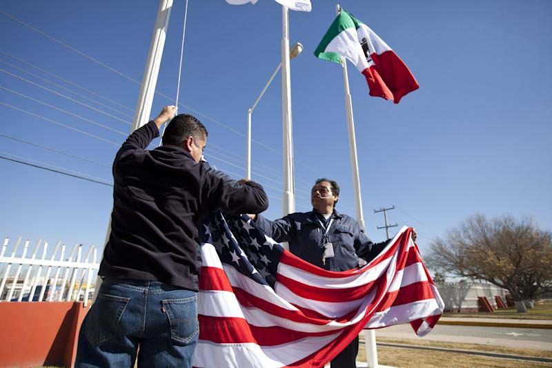In this Friday, Dec. 27, 2013 photo, workers at one of maquiladoras of the TECMA group prepare to raise the U.S. flag along with the Mexican and TECMA flags in Ciudad Juarez, Mexico. TECMA currently has 14 maquiladora plants in Ciudad Juarez. With the implementation of the North American Free Trade Agreement twenty years ago, many North American and international companies have moved their manufacturing to Mexico at a lower cost and while a majority of Mexicans have seen little benefit in income. While there is undoubtedly a larger middle class today, Mexico is the only major Latin American country where poverty also has grown in recent years. (AP Photo/Ivan Pierre Aguirre)