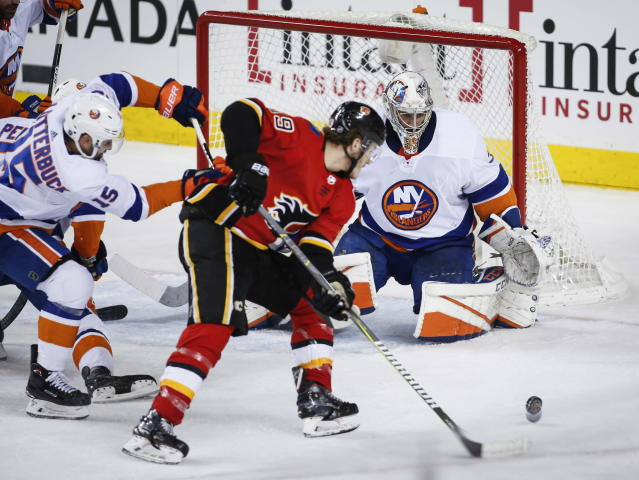 New York Islanders goalie Christopher Gibson, right, of Finland, looks on as Calgary Flames' Matthew Tkachuk swipes at a rebound during second-period NHL hockey game action in Calgary, Alberta, Sunday, March 11, 2018. (Jeff McIntosh/The Canadian Press via AP)