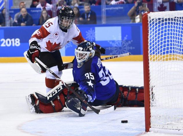Canada's Melodie Daoust, left, scores past USA's Madeline Rooney during the shootout in the gold medal women's hockey game.