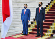 In this photo released by Indonesian Presidential Palace, Japanese Prime Minister Yoshihide Suga, left, and Indonesian President Joko Widodo listen to the national anthems during their meeting at the Presidential Palace in Bogor West Java, Indonesia, Tuesday, Oct 20, 2020. (Laily Rachev/Indonesian Presidential Palace via AP)