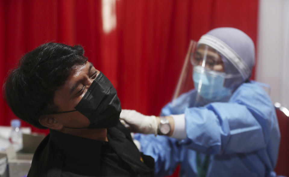 A man receives an injection of the AstraZeneca vaccine during a vaccination campaign in Bekasi outside Jakarta, Indonesia, Thursday, June 17, 2021. (AP Photo/Achmad Ibrahim)