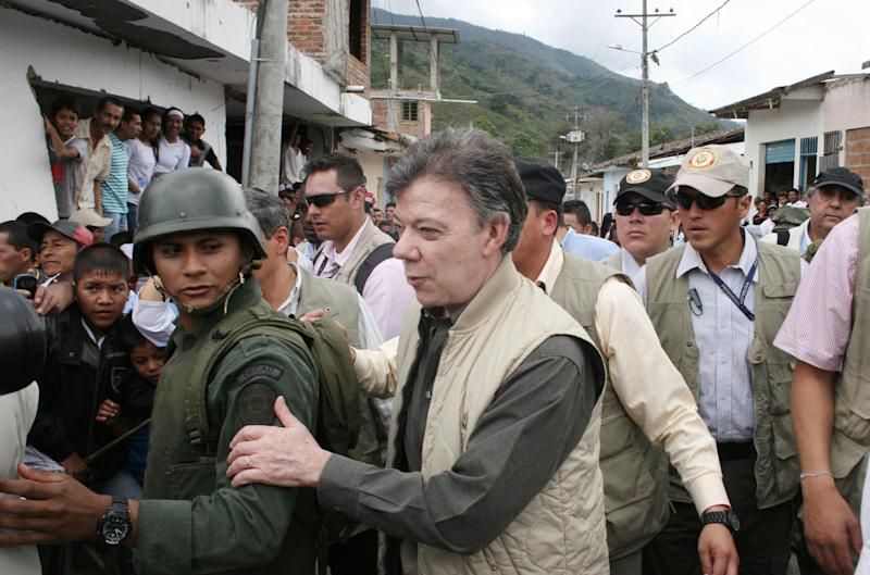 President Juan Manuel Santos holds onto a a police officer upon his arrival to Toribio, southern Colombia, Wednesday, July 11, 2012. Santos visited the town, that was attacked by rebels of the Revolutionary Armed Forces of Colombia, FARC, last week. (AP Photo/Juan Bautista Diaz)