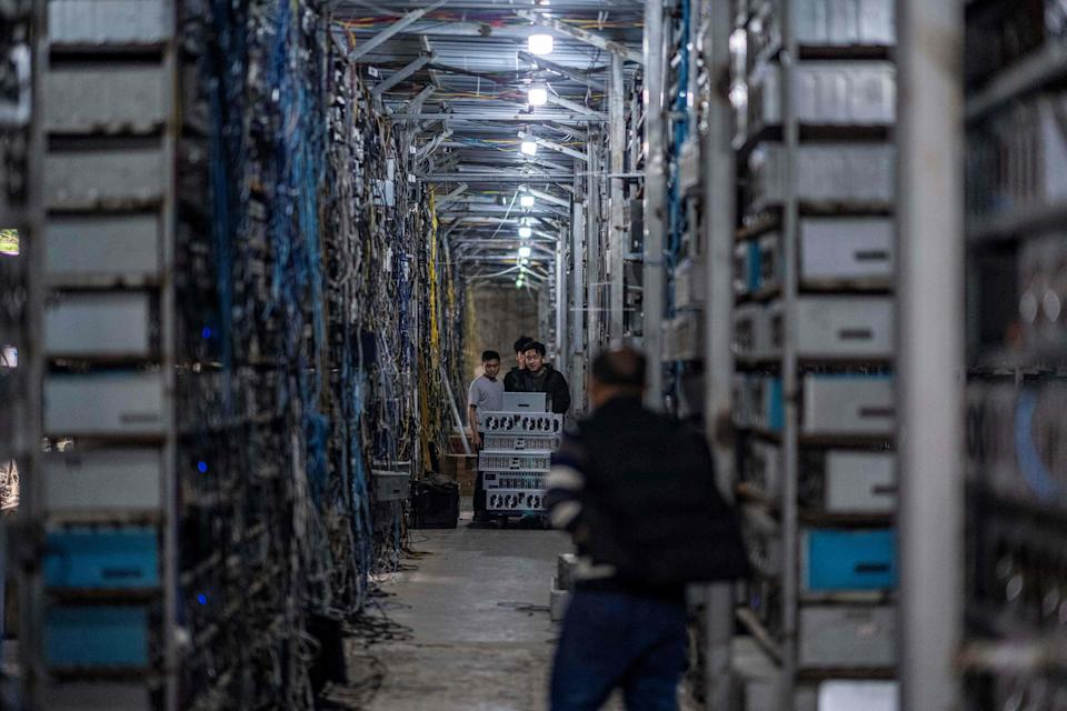Workers transferring cryptocurrency mining rigs in Dujiangyan in China's southwestern Sichuan province (AFP via Getty Images)