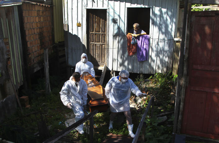 A family member watches as public funeral service workers remove the body of Amelia Dias Nascimento, 94, who died from complications related to COVID-19 in her home, in Manaus, Amazonas state, Friday, Jan. 22, 2021. The number of people who die in their homes amid the new coronavirus pandemic is growing due to the lack of availability in hospitals and the shortage of oxygen. (AP Photo/Edmar Barros)