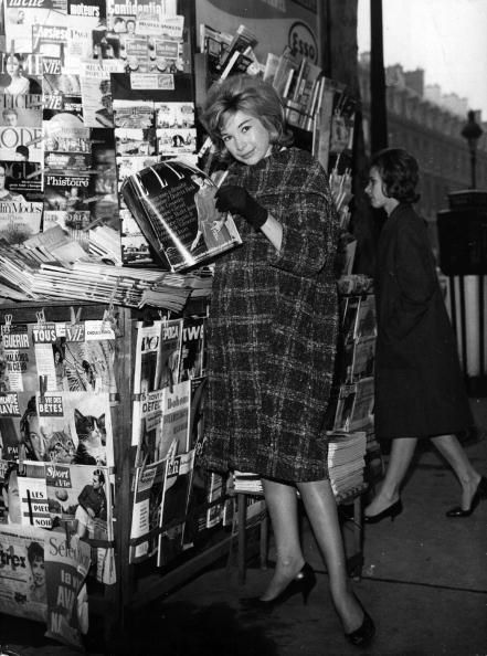 <p>The art of the trapeze coat swings back in action in 1964, with a classy updo to match. </p>