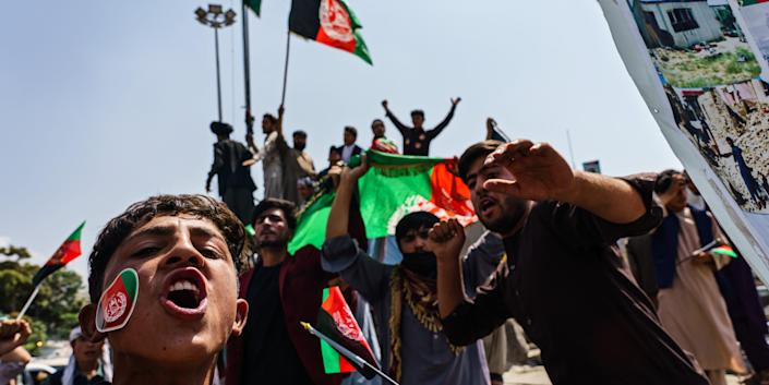 Afghans raise the national flag during a rally for Independence Day at Pashtunistan Square in Kabul, Afghanistan