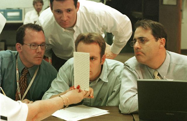 Election employees, reporters and Judicial Watch members look at undervotes in Fort Lauderdale, Fla., in 2000. (Photo: Robert King/Newsmakers/Getty images)