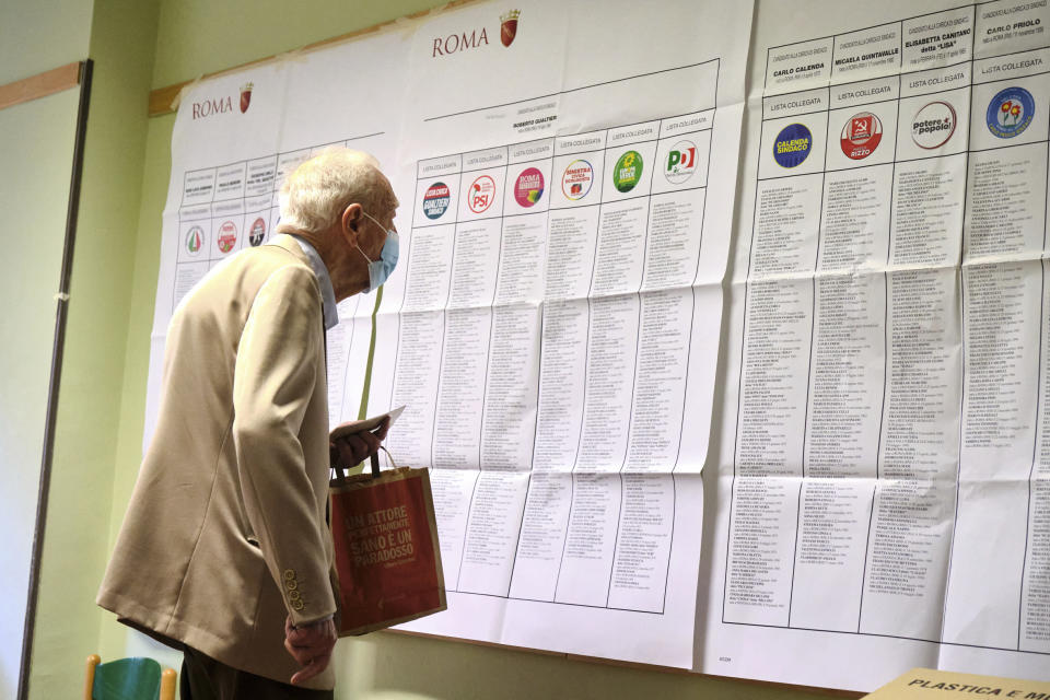 A man looks at candidates' names and party logos at a polling station, in Rome, Sunday, Oct. 3, 2021. Millions of people in Italy started voting Sunday for new mayors, including in Rome and Milan, in an election widely seen as a test of political alliances before nationwide balloting just over a year away. (Mauro Scrobogna/LaPresse via AP)