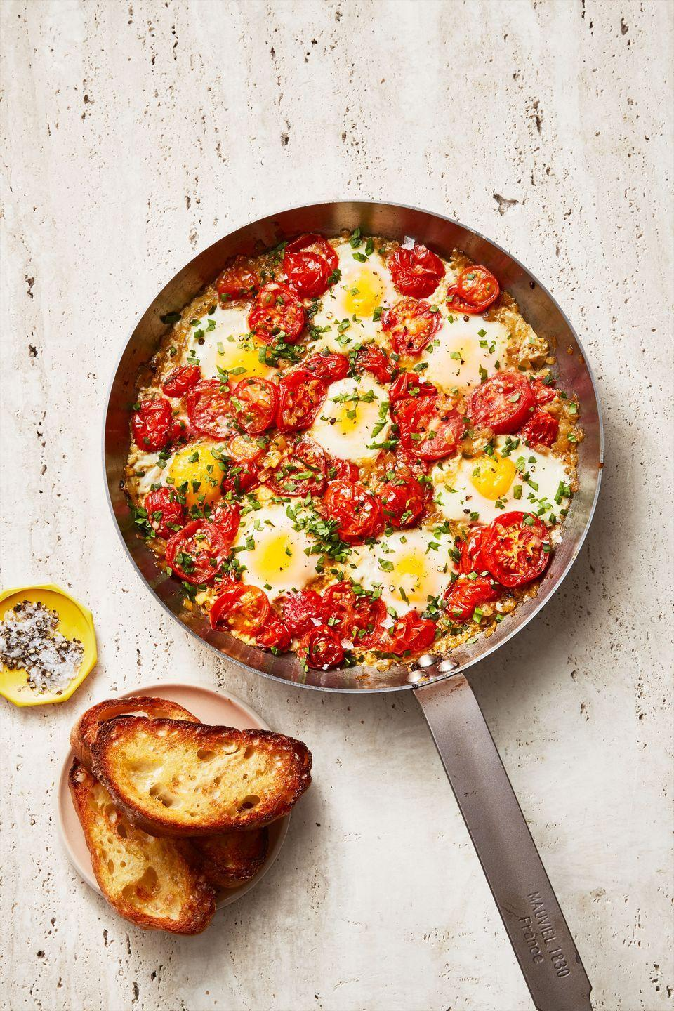 """<p>Tomatoes cooked with spices and onions until they're melt in your mouth, then topped with eggs and baked, make this comfort food for any time of day. Serve with toasts or pita for sopping up every last bit of the umami-packed sauce.</p><p><em><a href=""""https://www.goodhousekeeping.com/food-recipes/a34908201/easy-shakshuka-recipe/"""" rel=""""nofollow noopener"""" target=""""_blank"""" data-ylk=""""slk:Get the recipe for Shaksuka »"""" class=""""link rapid-noclick-resp"""">Get the recipe for Shaksuka »</a></em></p>"""