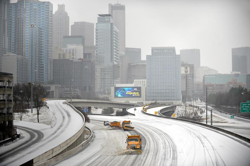 """Snow plows clear Interstate 75/85 on the downtown connector while transportation and business grinds to a halt during a winter storm on Wednesday, Feb. 12, 2014, in Atlanta. Across the South, winter-weary residents woke up Wednesday to a region encased in ice, snow and freezing rain, with forecasters warning that the worst of the potentially """"catastrophic"""" storm is yet to come. (AP Photo/David Tulis)"""