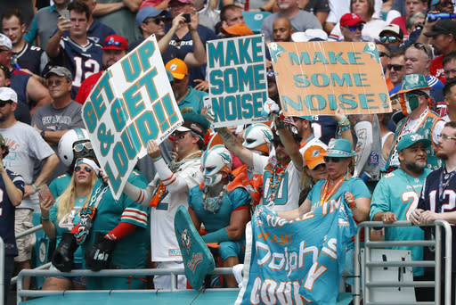 FILE - In this Sunday, Sept. 15, 2019 file photo, Miami Dolphins fans cheer the team, during the first half at an NFL football game against the New England Patriots, in Miami Gardens, Fla. The Miami Dolphins NFL football team has decided to allow up to 13,000 socially distancing fans to attend their home opener against the Buffalo Bills on Sept 20, with the approval of state and local political leaders. (AP Photo/Wilfredo Lee, File)