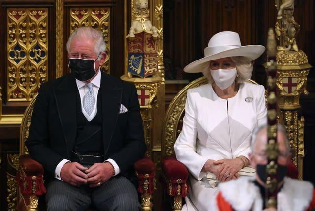 The Prince of Wales and the Duchess of Cornwall listen as the Queen delivers the speech