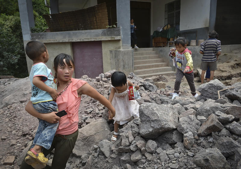 A woman brings the children evacuate from an earthquake hit Luozehe town in Yiliang county in southwest China's Yunnan province Saturday, Sept. 8, 2012. Authorities poured aid into a remote mountainous area of southwestern China and rescue workers with sniffer dogs searched for survivors Saturday after twin earthquakes killed at least 80 people. (AP Photo) CHINA OUT