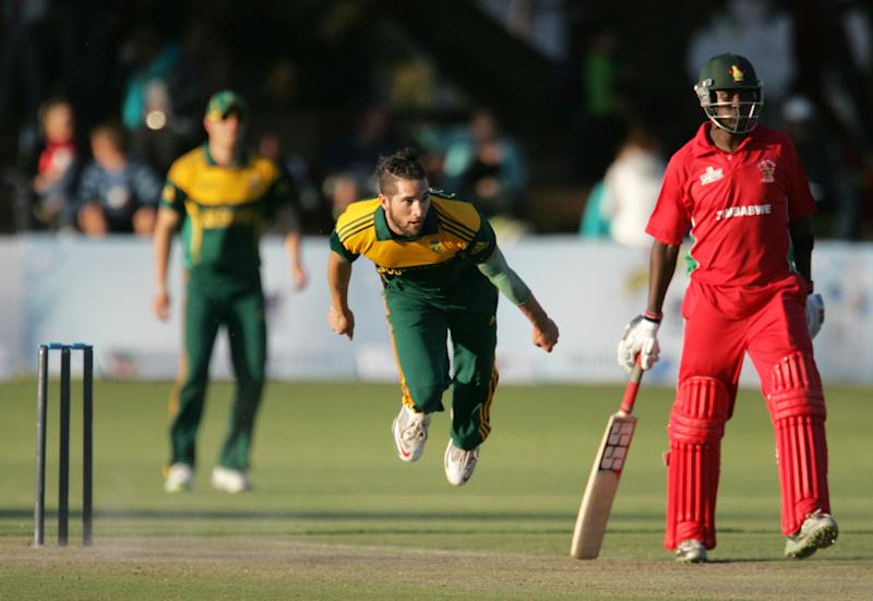 South Africa's bowler Wayne Parnell (C) is seen in action as Zimbabwe's captain Elton Chigumbura (R) looks on at the Queens Sports Club, Bulawayo, August 17, 2014