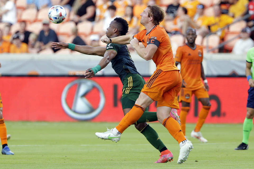 Portland Timbers forward Jeremy Ebobisse, left, and Houston Dynamo defender Tim Parker, right, bring down the ball during the first half of an MLS soccer match Wednesday, June 23, 2021, in Houston. (AP Photo/Michael Wyke)