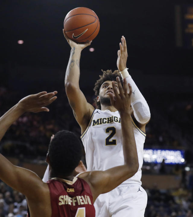 Michigan forward Isaiah Livers (2) shoots over Elon guard Marcus Sheffield II during the second half of an NCAA college basketball game Friday, Nov. 15, 2019, in Ann Arbor, Mich. (AP Photo/Carlos Osorio)