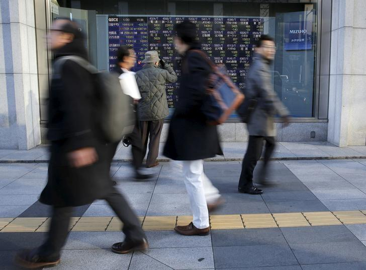 A man (3rd L) looks at an electronic stock quotation board as passers-by walk past, outside a brokerage in Tokyo, Japan January 20, 2016. REUTERS/Toru Hanai/Files