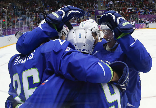 Team Slovenia celebrate a goal against Slovakia in the third period of a men's ice hockey game at the 2014 Winter Olympics, Saturday, Feb. 15, 2014, in Sochi, Russia. (AP Photo/Julio Cortez)