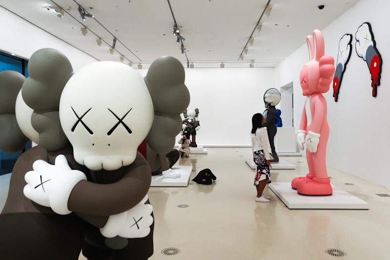 MELBOURNE, AUSTRALIA - SEPTEMBER 19: A visitor looks at a sculpture by KAWS during a media preview of KAWS: Companionship in the Age of Loneliness Exhibition Opening at National Gallery of Victoria at National Gallery of Victoria on September 19, 2019 in Melbourne, Australia. (Photo by Asanka Ratnayake/Getty Images)