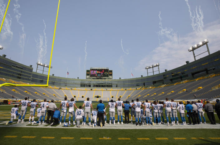 FILE - Detroit Lions players stand and kneel during the National Anthem before their NFL football game against the Green Bay Packers in Green Bay, Wisc., in this Sept. 20, 2020, file photo. The national anthem would have to be played before all sporting events at Lambeau Field, the Fiserv Forum and all other Wisconsin venues that have received taxpayer money under a bill introduced Thursday, Feb. 25, 2021, in the state Legislature by a Republican lawmaker. (AP Photo/Jeffrey Phelps, File)