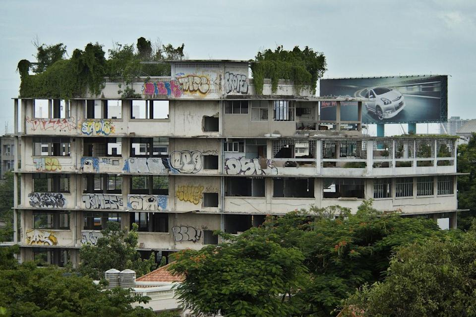 <p>Grass and graffiti have overtaken an uninhabited apartment building.</p>