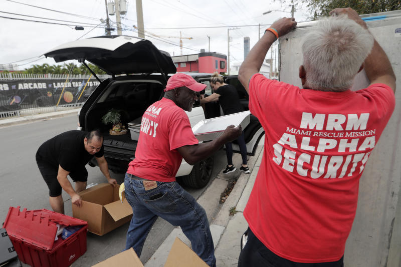 In this Thursday, Feb. 20, 2020 photo, Julio Yon, left, owner of Cuban Boys, and William Friday, center, of the Miami Rescue Mission,, unload food for the burger bash competition at the Miami Rescue Mission in Miami. From Rachael Ray to Bobby Flay, the biggest names in the culinary world are in Miami starting Thursday for the South Beach Wine and Food Festival. And they're getting help in their prep kitchen from an unlikely source, a local homeless shelter. The festival partnered with the Miami Rescue Mission and Florida International University's culinary school. (AP Photo/Lynne Sladky)