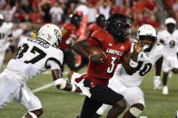 Louisville quarterback Malik Cunningham (3) runs through the defense of Central Florida linebackers Eriq Gilyard (10) and Eriq Gilyard (10) during the second half of an NCAA college football game in Louisville, Ky., Friday, Sept. 17, 2021. (AP Photo/Timothy D. Easley)